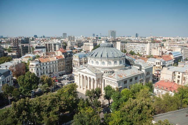 Ateneul Român, una dintre cele mai vechi și frumoase clădiri din București, în contrast cu zona nou construită dinf undal. În imagine (centru) se vede și cea mai înaltă clădire din oraș, Sky Tower.